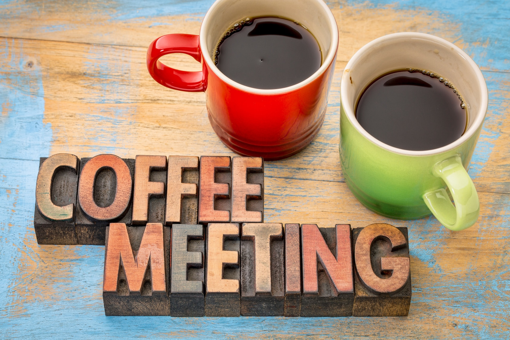 coffee meeting concept - text in vintage letterpress wood type printing blocks with two cups of coffee